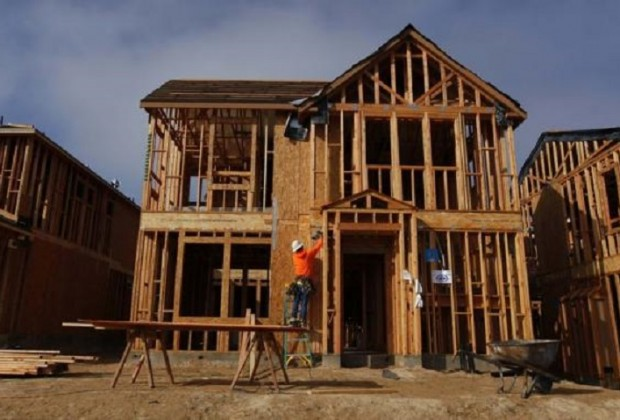 A construction worker is seen building single family homes in San Diego