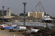 A man walks past steel rims and parked cars at a dock yard at Mumbai Port Trust in Mumbai